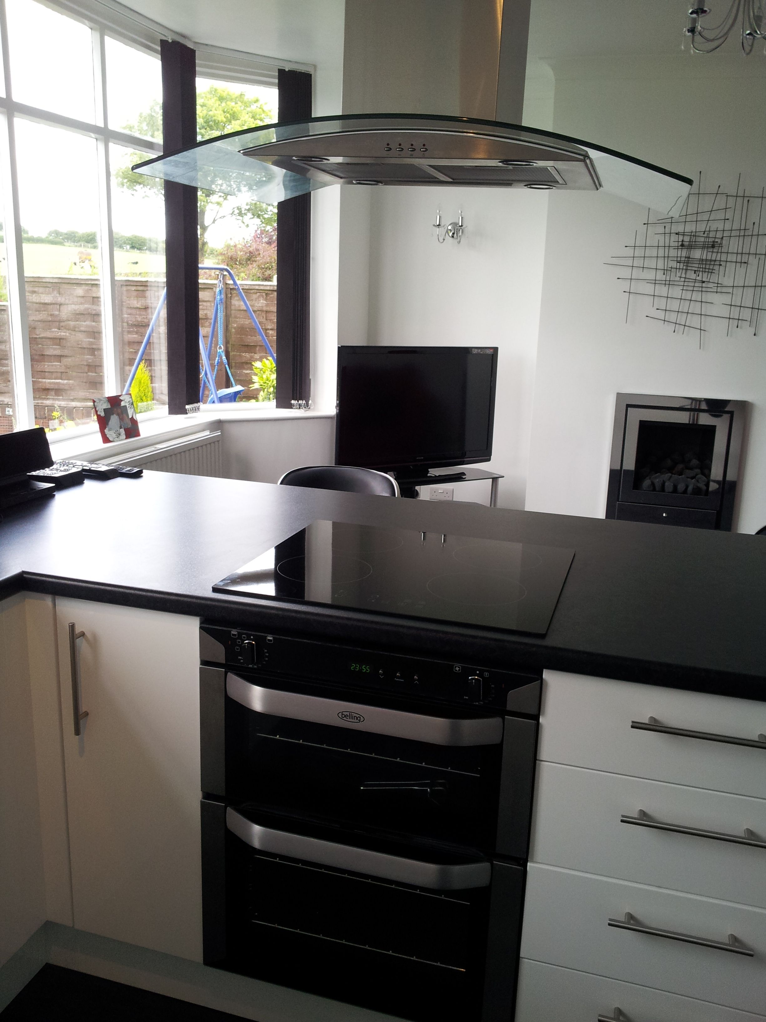 Sleek Modern Black White Kitchen With Breakfast Bar Gl Island Hood Integrated Double Oven Induction Hob
