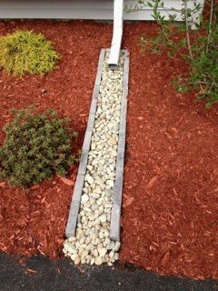 Downspout Water Run Off Keeps Mulch Contained In Flower Beds