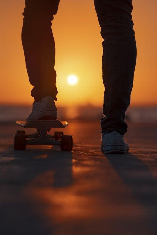 selective focus photo of person standing on skateboard during golden hour selective focus photo of person standing on skateboard during golden hour Skateboard