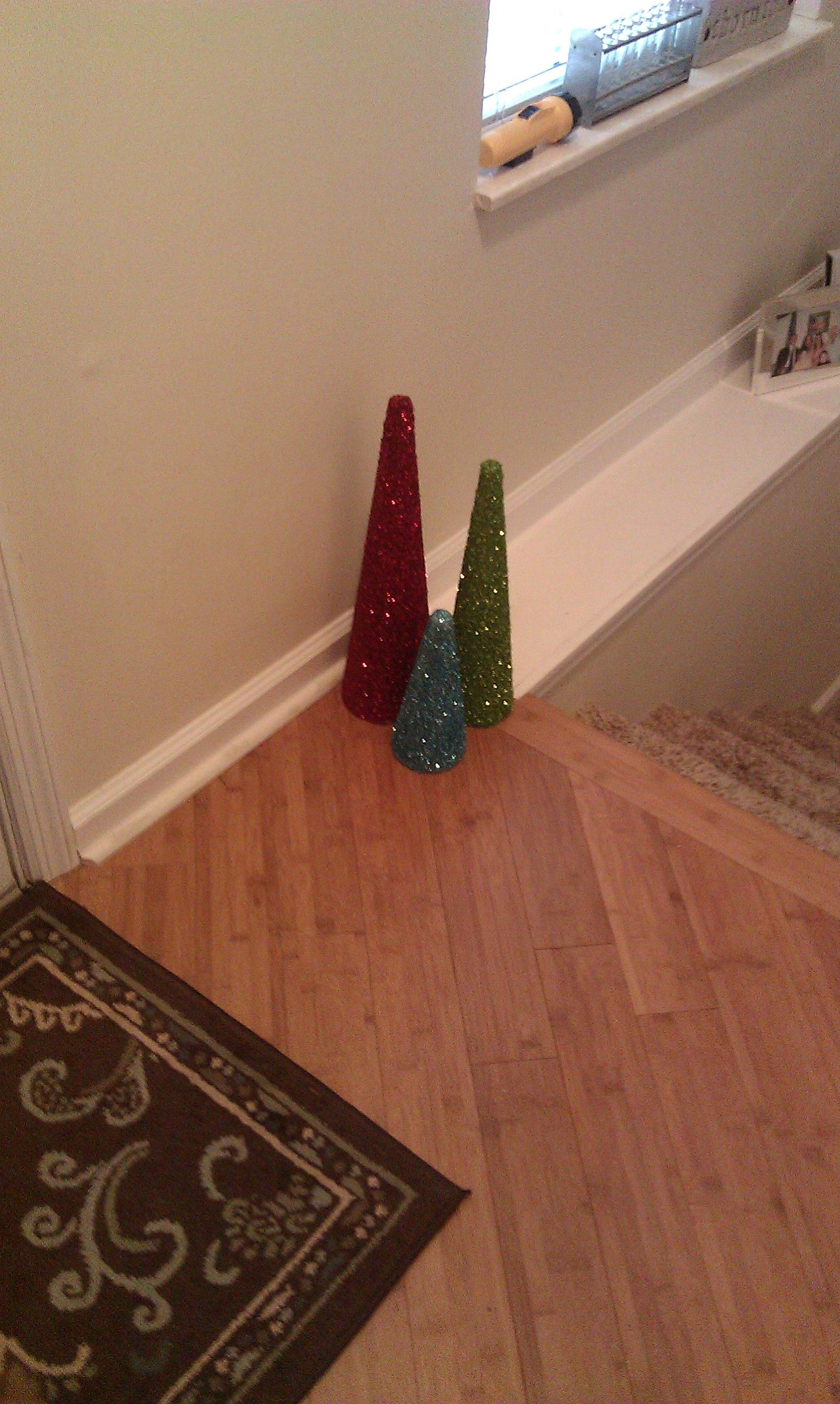 diy christmas glitter trees...just buy the styrofoam cones, spray adhesive glue all over, and cover with your fave glitter!