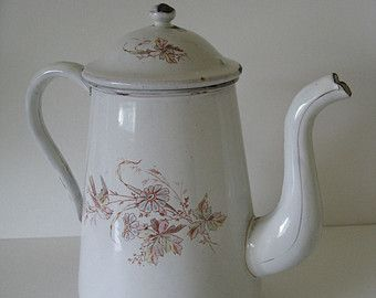 Pretty French coffee pot in milky white enamelware gold gilt trim on spout and seamed handle (fading) with floral bouquets design in blues, greens, yellow, and purple circa 1930s  Very good vintage condition most visible spot of enamel loss at top of lid (see photos) and at bottom base to be expected from age and useage water tight, no holes  Measures approx 8.75 tall x 9.75 spout to handle