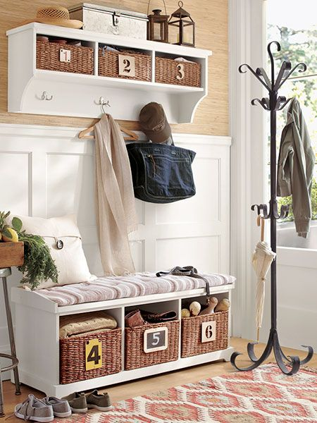 Here, a storage bench combines with a wall shelf and a coat tree for a wallet-friendly setup that's as functional as a built-in. Wainscoting acts as a bench back and ties the pieces together.