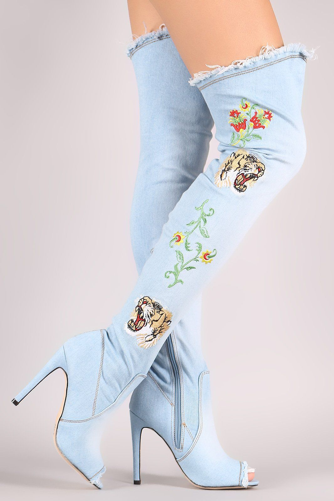 3cb24b2697c These over-the-knee boots feature a frayed detailing at front and top  opening. Embroidered floral and tiger head embellishment at side. Peep toe  silhouette ...