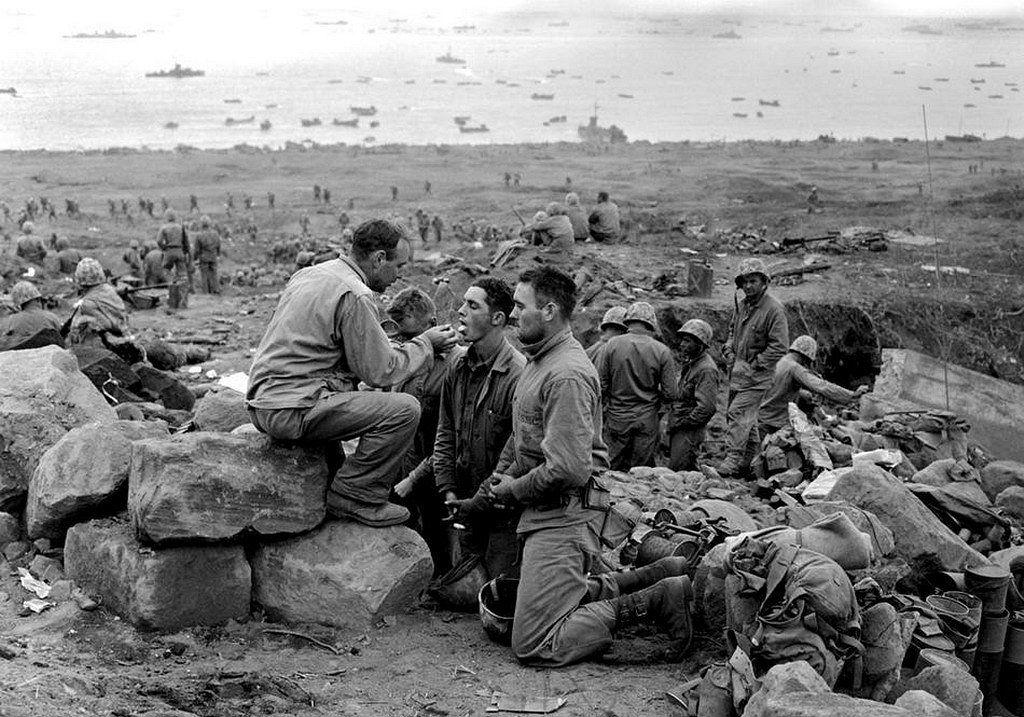 World War II, Pacific Ocean, Iwo Jima, Bonin Islands, March 3, 1945 - U.S. Marines receive Communion from a U.S. Marine Corps chaplain on the beach during the Battle of Iwo Jima (Operation Detachment)