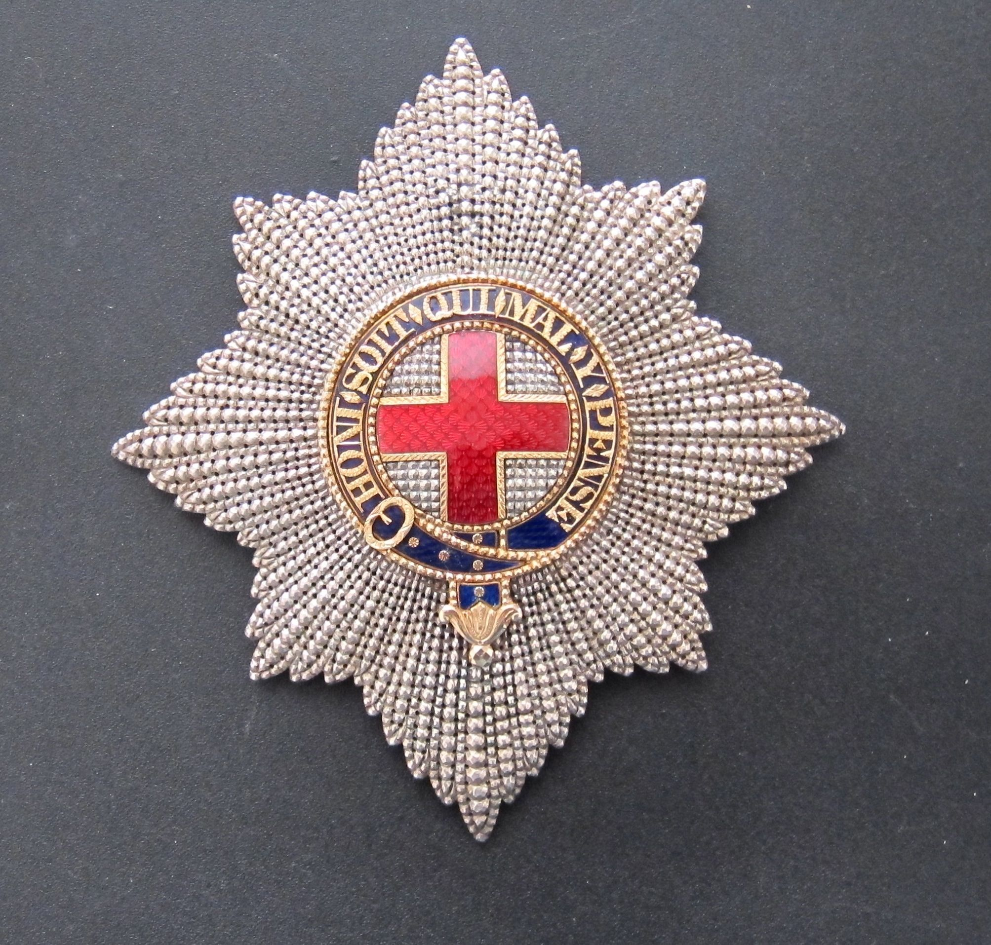 The star of the Order of the Garter, which is worn pinned to the left breast, was introduced in the 17th century by King Charles I and is a colourfully enamelled depiction of the heraldic shield of St. George's Cross, encircled by the Garter, which is itself encircled by an eight-point silver badge.