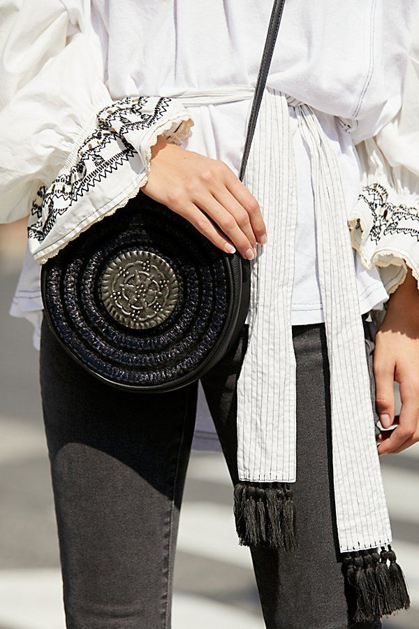 39fbe0fd311 Tambourine Roundy Bag by Free People - Raffia round crossbody style bag  trimmed with faux leather.   Etched metal accent in the center   Zip top  closure ...