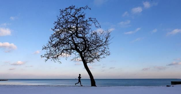 A runner jogs along Lake Michigan at the North Avenue beach in Chicago on Tuesday as temperatures hover around freezing.