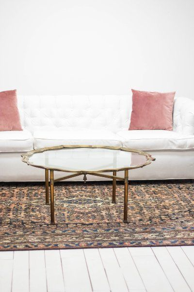 Tufted white linen sofa with mauve velvet throw pillows brass coffee table glass top intricate pink and blue antique persian rug via birch also