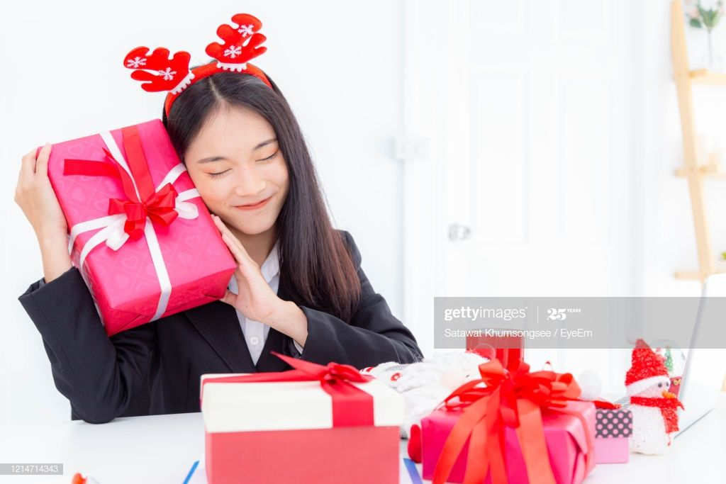 Businesswoman With Eyes Closed Holding Christmas Presents While Sitting At Desk #Ad, , #affiliate, #Closed, #Holding, #Businesswoman, #Eyes