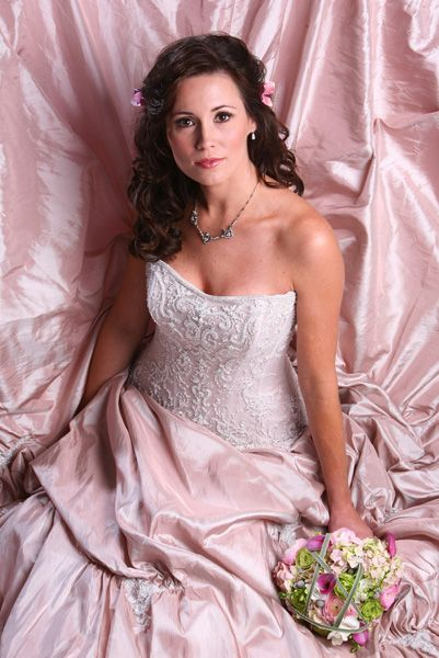 Pink wedding gown with roses in her hair down wedding hair; wedding makeup