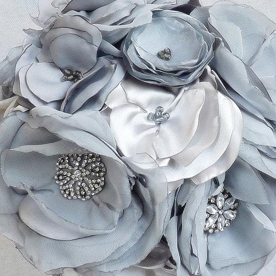 Opvallend alternatieve boeket bloemen van de functies in tinten van grijs en zilver met strass en brokaat accenten. Elke bloem is geweest zorgvuldig handgemaakt uit lagen van satijn en chiffon die kaars-geschroeid zijn. Gewatteerde handvat is stof-omwikkeld met een zwart en zilver