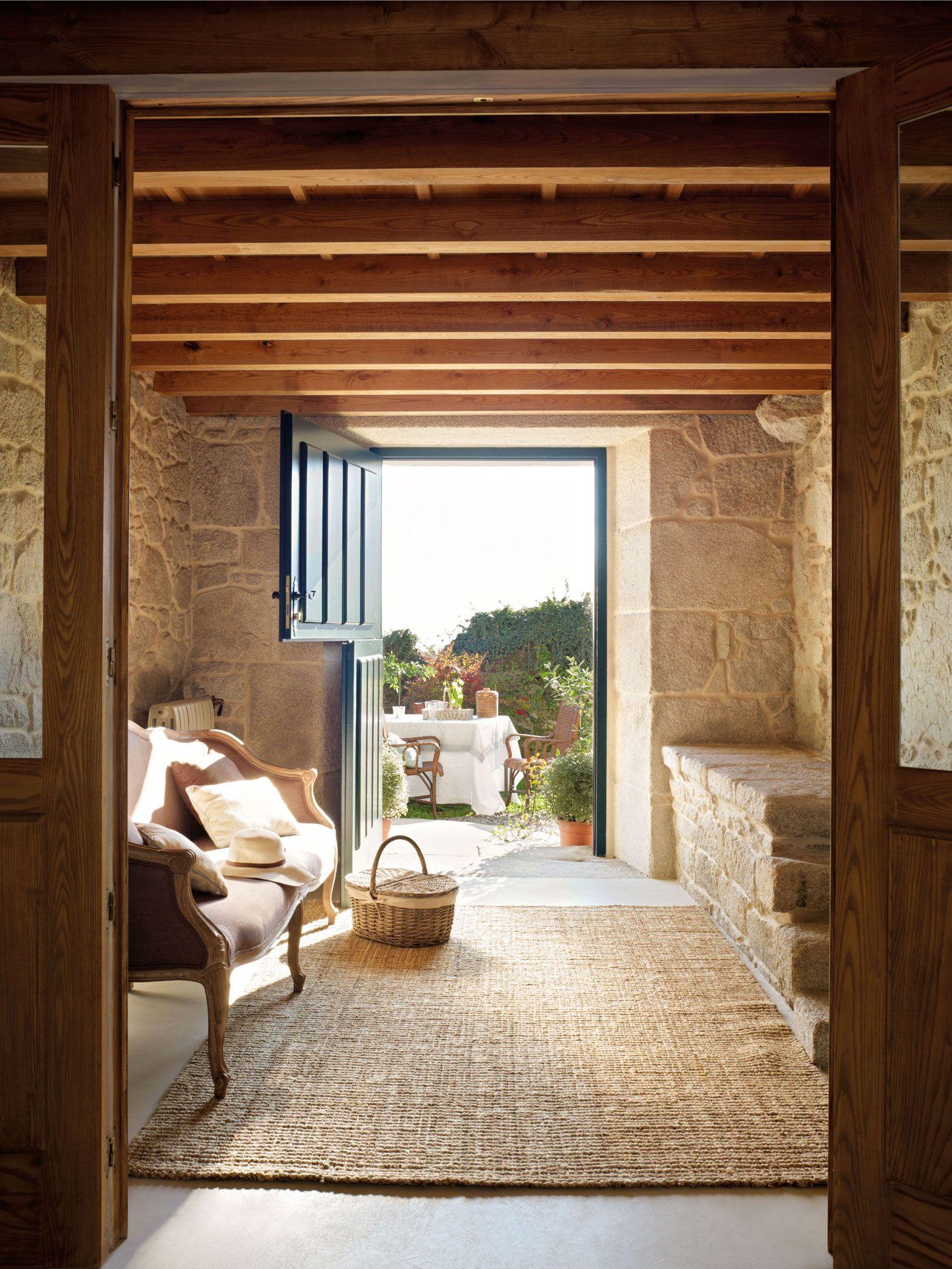 Entrada de la casa con muros de piedra y un banco sobre una alfombra ...
