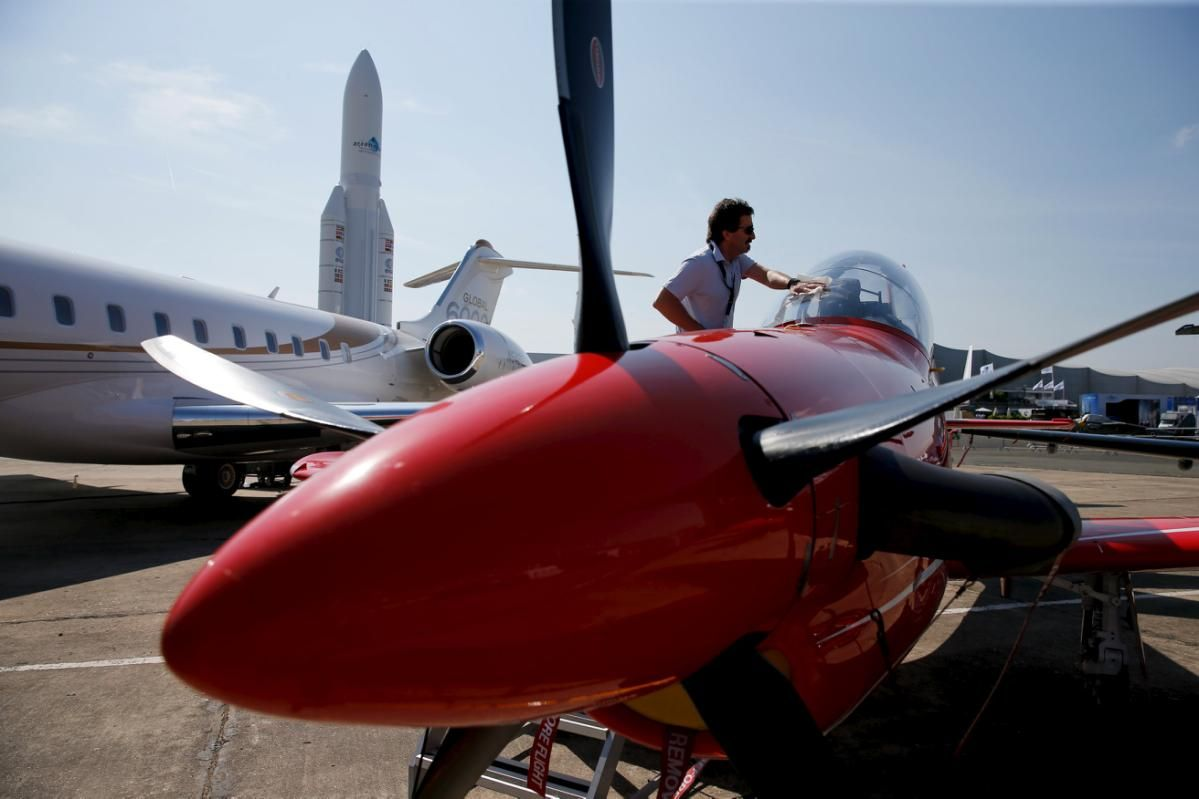 A worker cleans the cockpit of a Pilatus PC-21 on a static display two days before the opening of the 51st Paris Air Show at Le Bourget airport near Paris