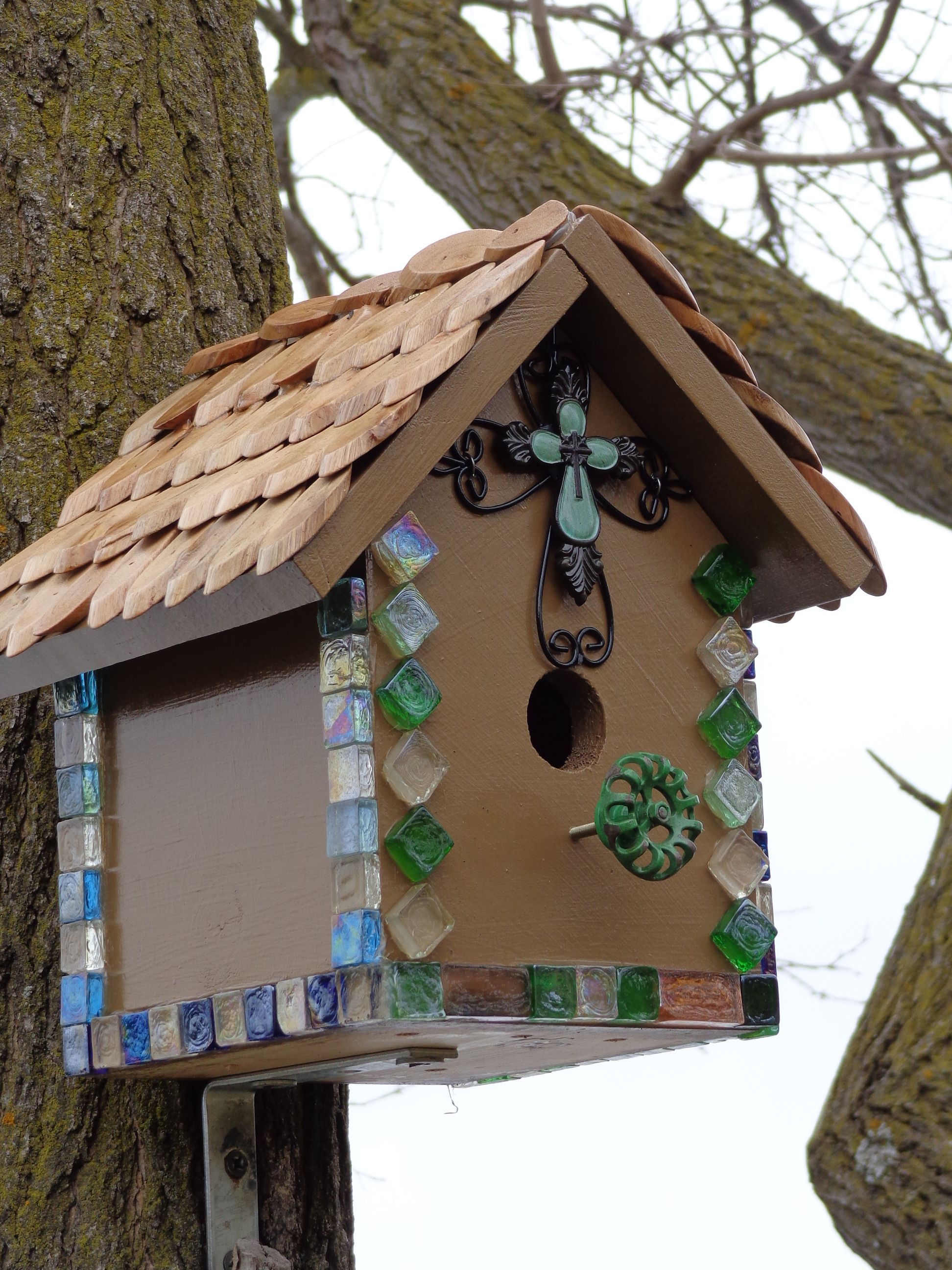 Brown birdhouse with glass tiles for trim and wood chips