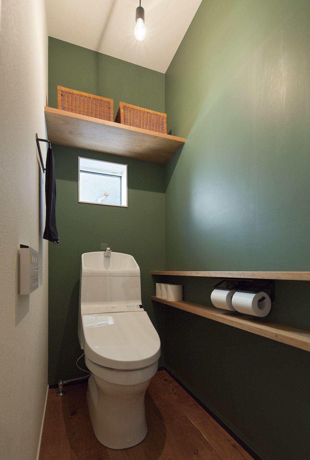 グリーンのアクセントクロスにブラックチェリーの床と棚板 アイアンのタオル掛けにbare Light Bulb クロスに合わせて色を変えた巾木 世界で一番落ち着ける場所を 最大限のコーディネートを施された空間 トイレ おしゃれ トイレ 壁紙 おしゃれ シンプル トイレ