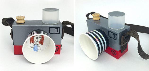 Para hacer esta cámara necesitas una caja de cartón pequeña, un vaso desechable de cartón, una tapa redonda de algún bote de cosmética, abalorios, cinta americana (también puedes utilizar cinta aislante, por ejemplo), cinta adhesiva decorativa (washi tape), tijeras, pegamento y rotulador negro indeleble.