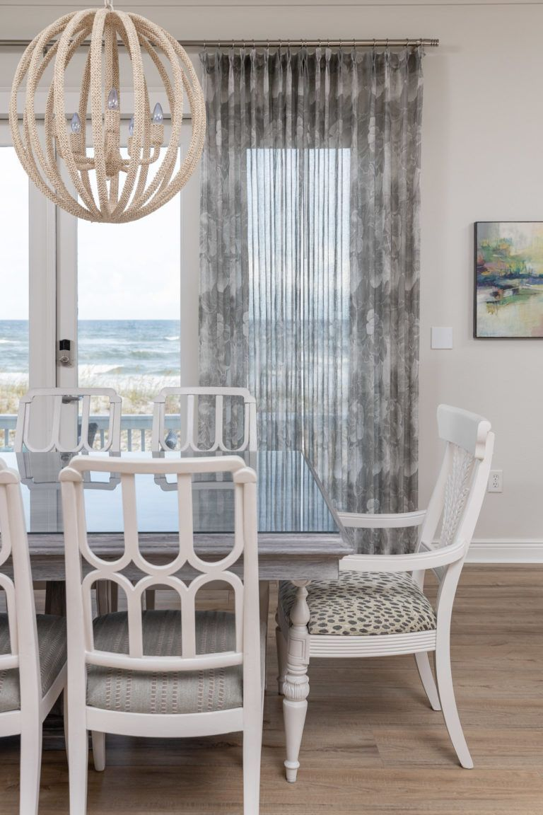 From poorly put together Tommy Bahama, to fresh with a nod to mod. This new dining room is perfect for entertaining - Designed by In Detail Interiors #diningroom #diningroomchairs #diningroomtable #design #interiordesign #whitediningchair #beadedchandelier #panels #sheerpanels #coastaldesign #coastaldiningroom #inspiration #inspo #diningroominspo #remodel #coastalremodel #coastalhome