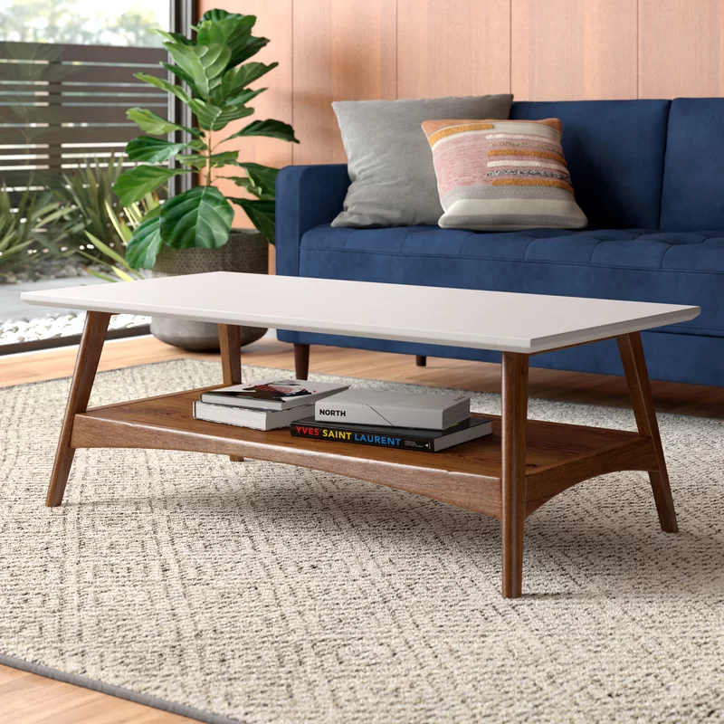 Coffee tables are like a noses, in that we don't think much about them, but without them things would look very strange. Don't let that happen to your living room, and grab this coffee table. Its mid-century modern silhouette is made from solid and engineered wood and features clean lines with tapered and splayed legs. The rectangular tabletop has a white finish, while the rest of the table is pecan brown for an on-trend two-tone look. And thanks to its two-tiered design, there is plenty of space to display plants and art books. Product Details Top Material:  Manufactured Wood Base Material:  Solid Wood Level of Assembly:  Partial Assembly Number of Tables Included:  1