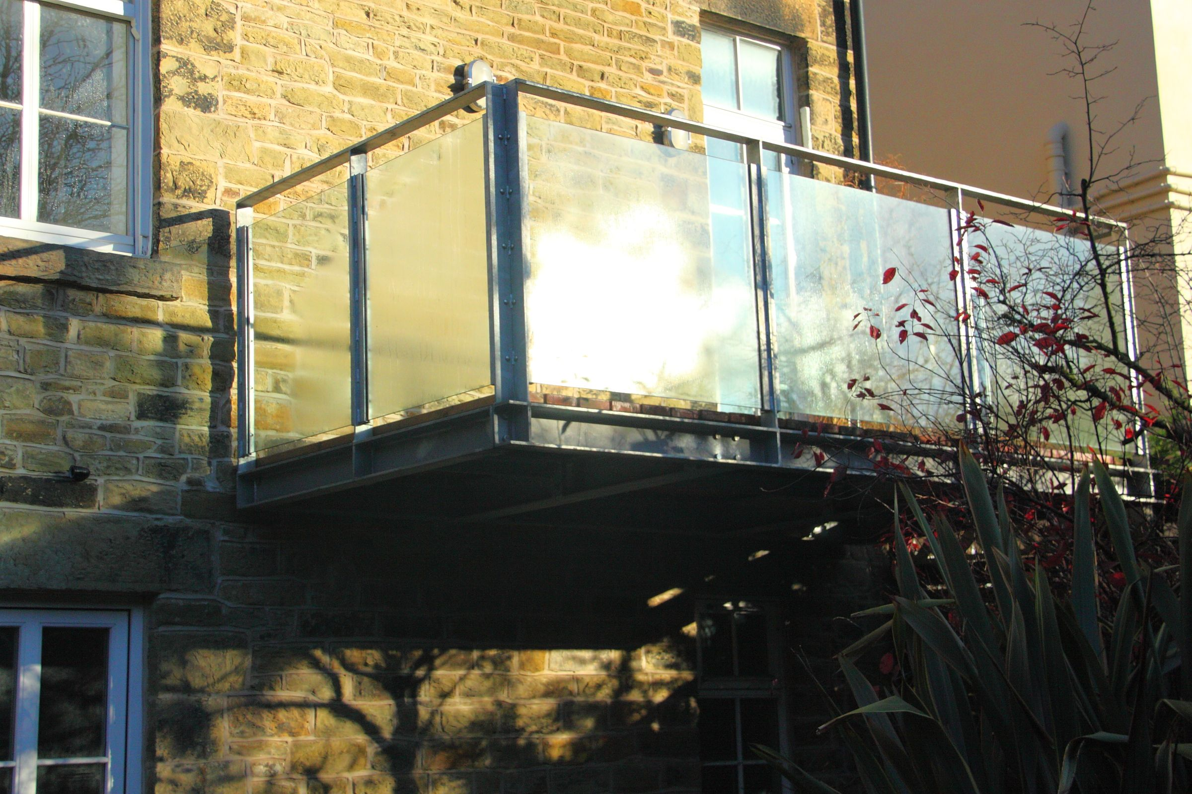 Design: Hughes Coates Architecture. Steel, glass and timber balcony on a Victorian detached villa in Sheffield. A modern minimalist design takes advantage of a sloping site to provide outdoor living for the raised ground floor.