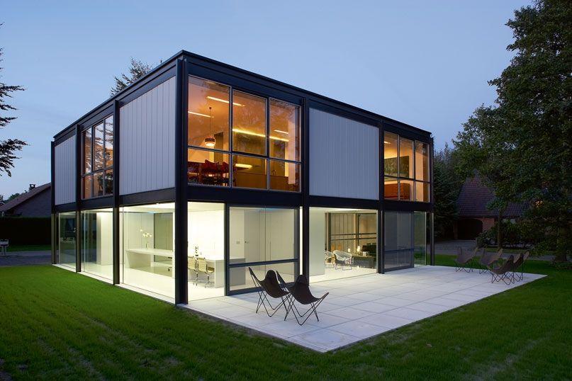 Casa de diseño al atardecer con ventanales que dejar entrar toda la - plan maison structure metallique