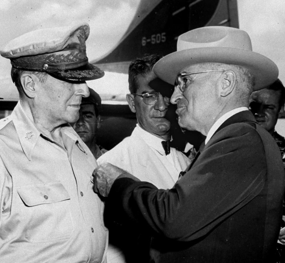 President Truman pins the Distinguished Service Medal with four oak leaf clusters on the shirt of General Douglas MacArthur during a ceremony at the airstrip on Wake Island, in this Oct. 14, 1950, file photo. In the center is John J. Muccio, United States ambassador to Korea, who was decorated with a Medal of Merit. According to a letter sent by Muccio to the State Department, U.S. soldiers would fire on refugees if they approached U.S. lines. The letter referred to a policy set down on July…
