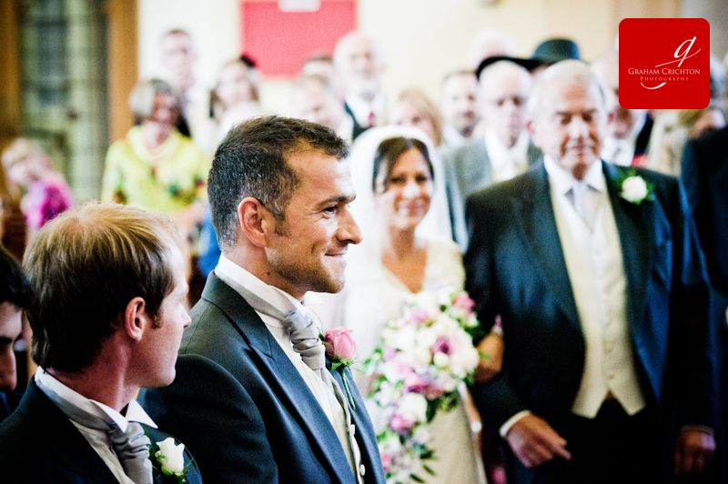close up shot of Groom smiling as the bride arrives at the front of the church with her father www.grahamcrichton.com