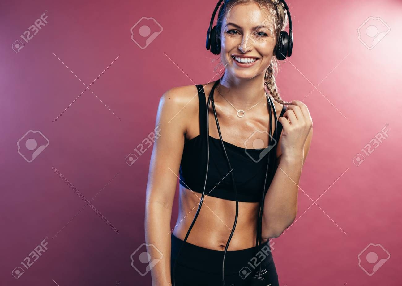 Fitness woman in sportswear and headphones on colored background. Smiling sports woman resting after...