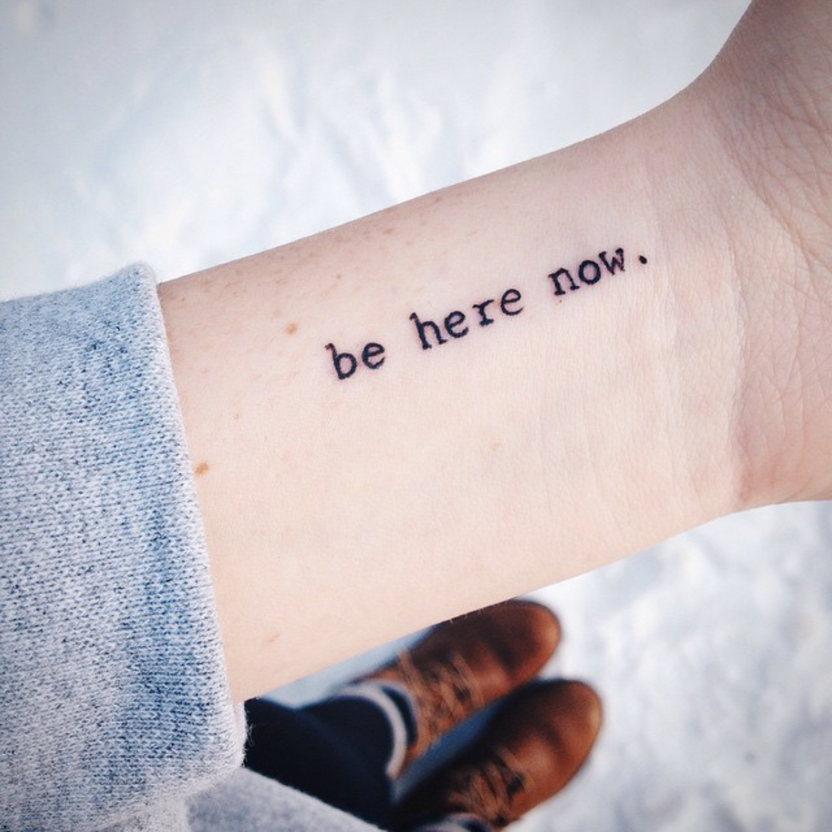"Peque±o tatuaje que dice ""Be here now"" frase en inglés que significa """