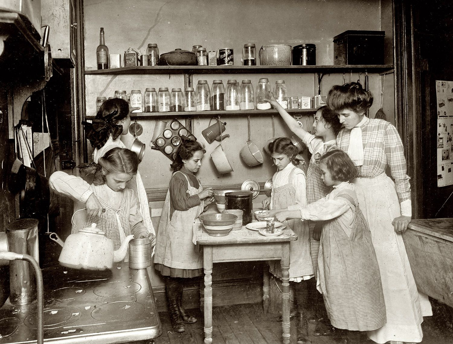 "In the Kitchen: 1910. ""Home economics in public schools. Kitchen in housekeeping flat, New York,"" circa 1910. National Photo Company Collection glass negative. (fiction) Lillie Mae Parkman (at table, left side) with her mother & sisters - early 1900's."