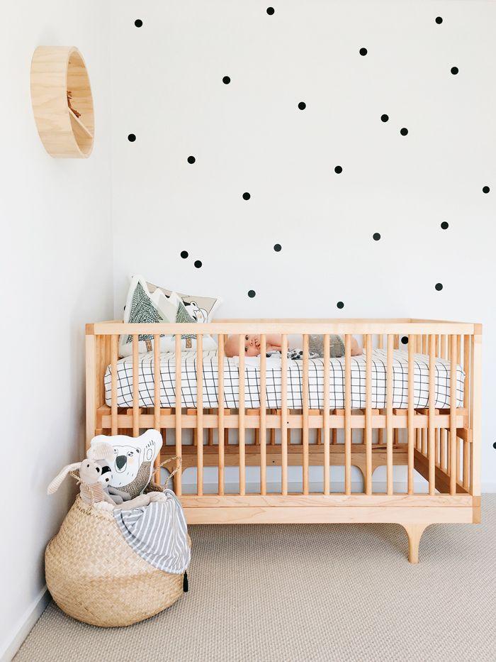 Habitación de bebé con stickers lunares, cuna de madera y estantería ...
