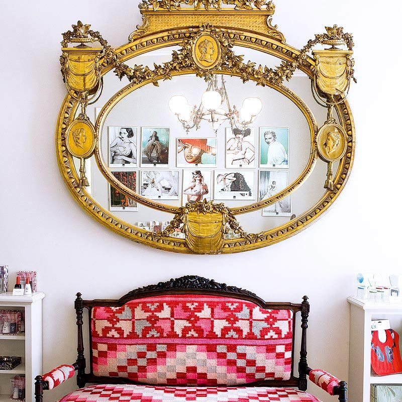 Antique gold mirror above red patterned bench