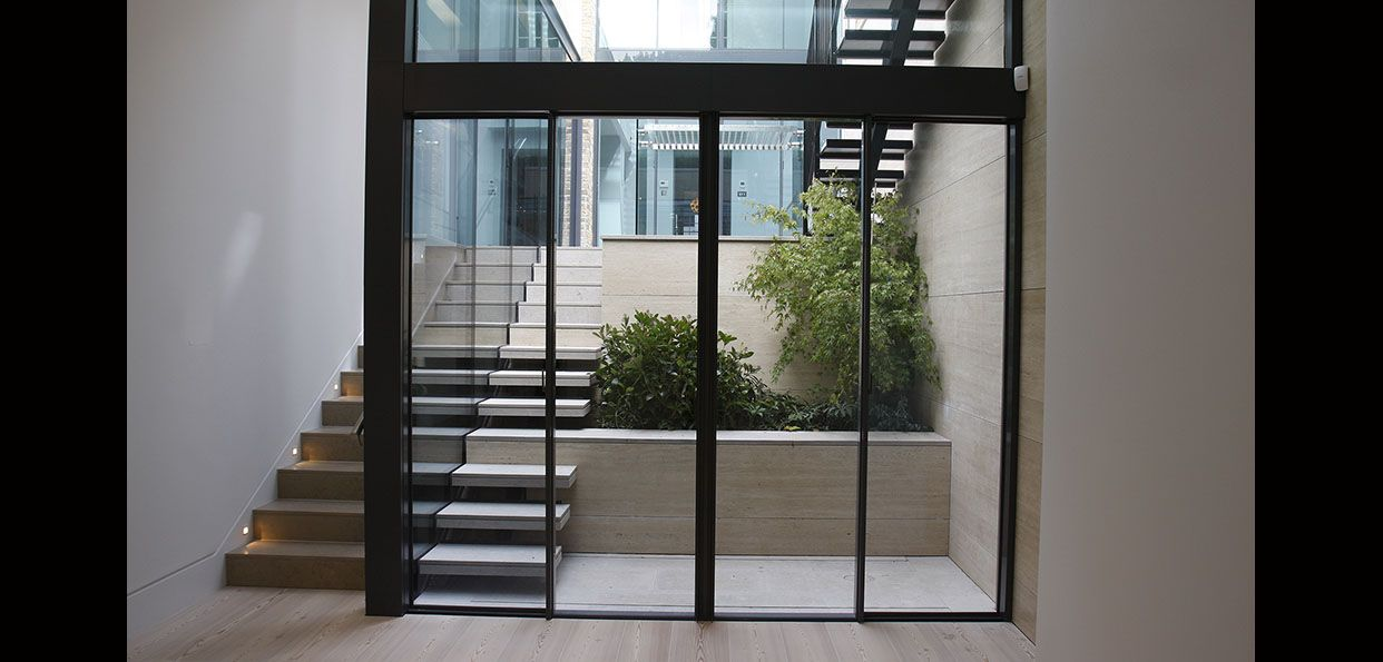 Minimally Framed Sliding Glass Doors With Heated Glass To Basement