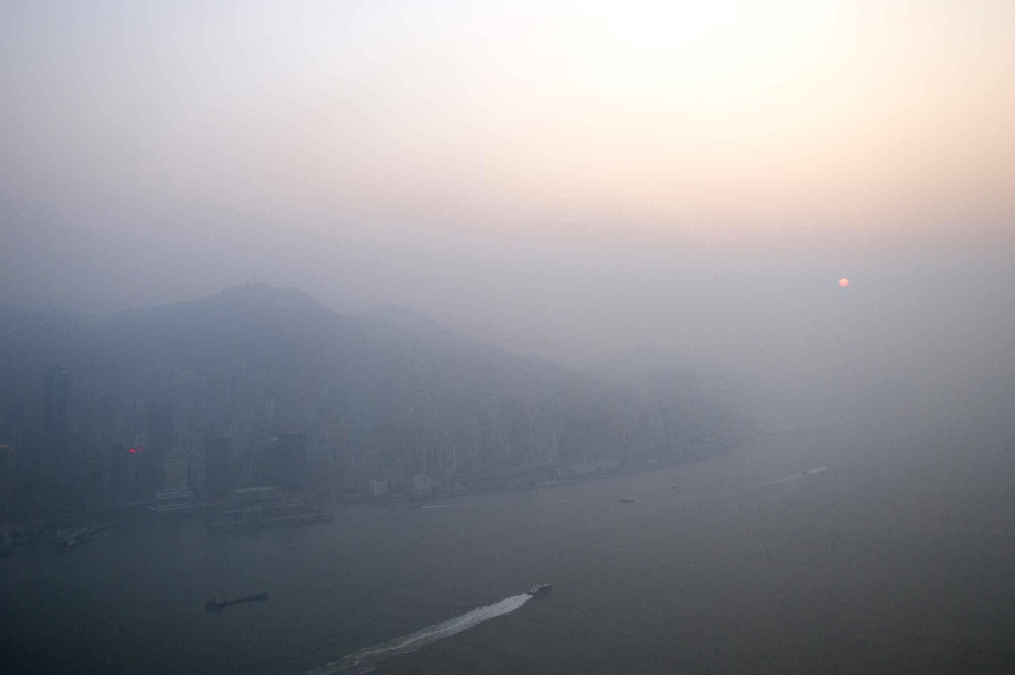 Le 5 janvier, le soleil se couche sous l'épaisse brouillard de pollution qui couvre la ville de Hong Kong.
