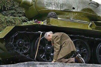 A Russian war veteran kneels beside the tank he spent the war in, now a monument.