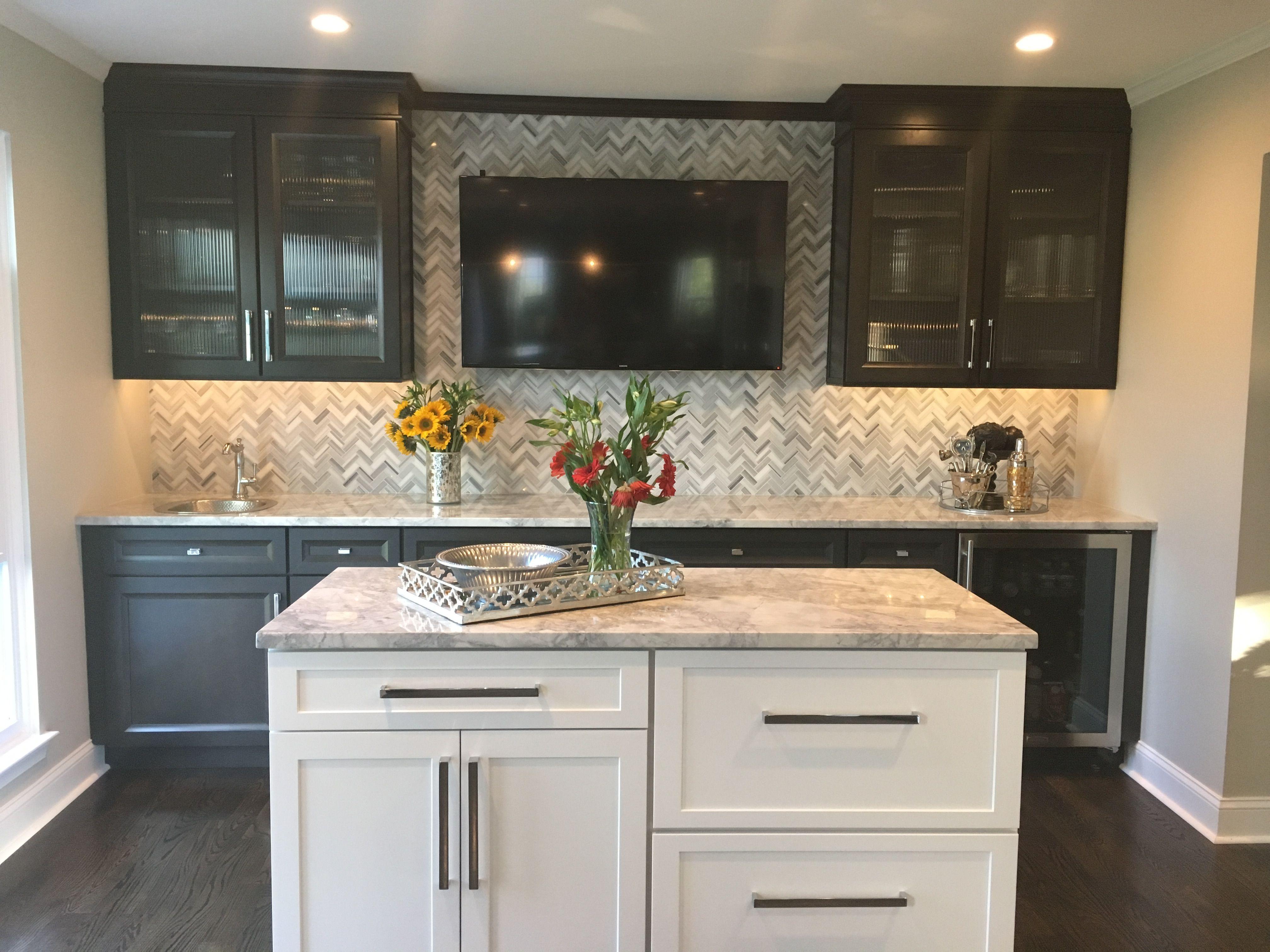wet bar with dark cabinets, gray and white herringbone backsplash