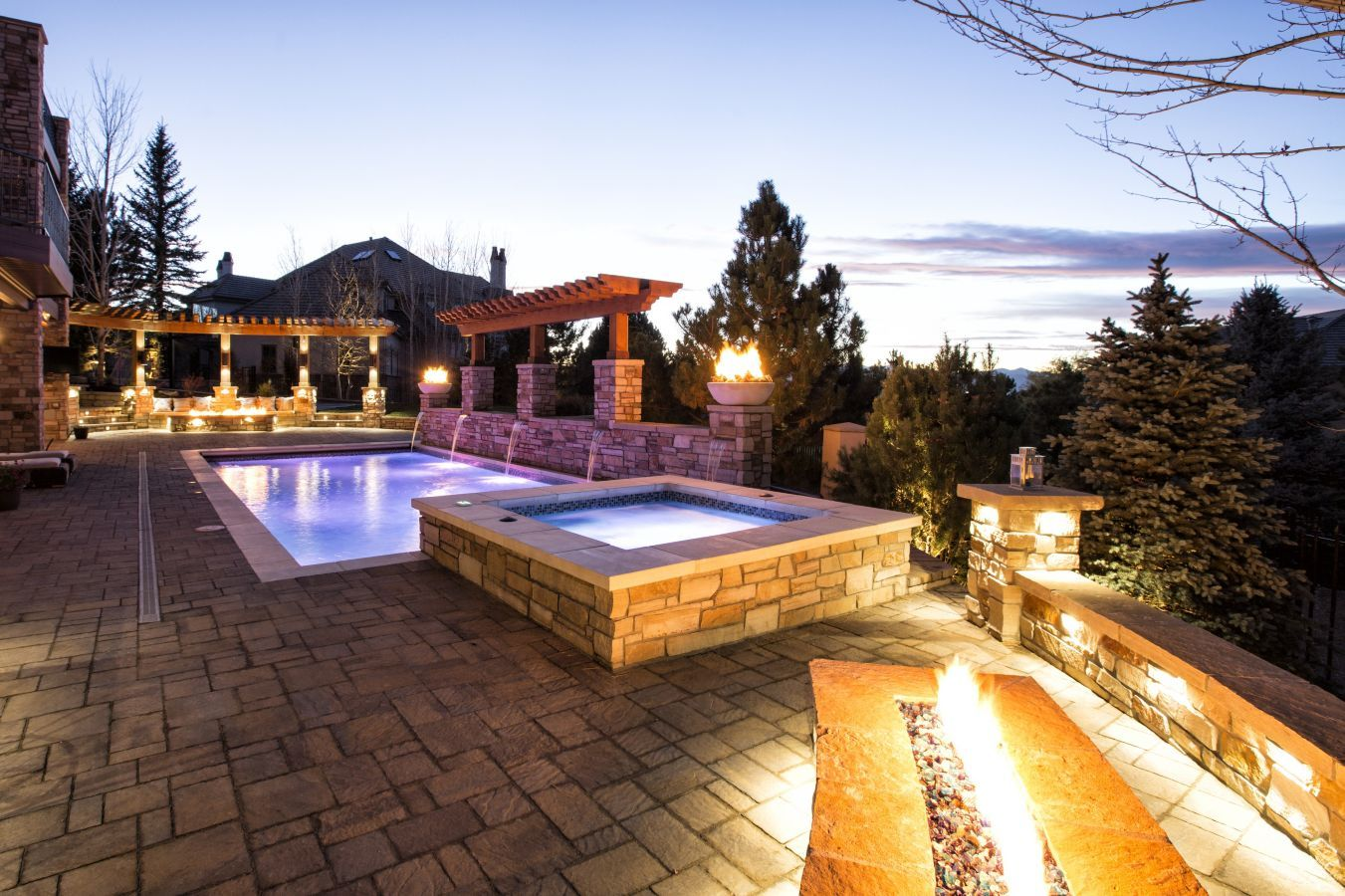 Open Fire Pits Stone Flooring And A Colorfully Lit Pool By Dream Makers Overlook The Rocky Mountains In This Hom Beautiful Pools Outdoor Design Pool Builders