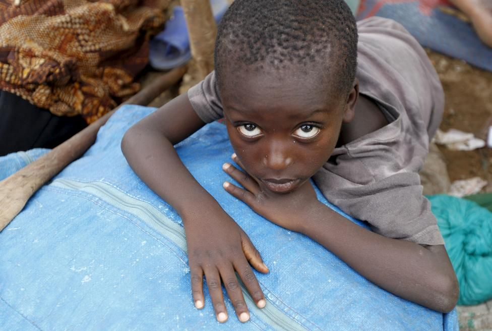 A Burundian refugee child rests on their belongings on the shores of Lake Tanganyika in Kagunga village in Kigoma region in western Tanzania, as they wait for MV Liemba to transport them to Kigoma township, May 18, 2015. REUTERS/Thomas Mukoya