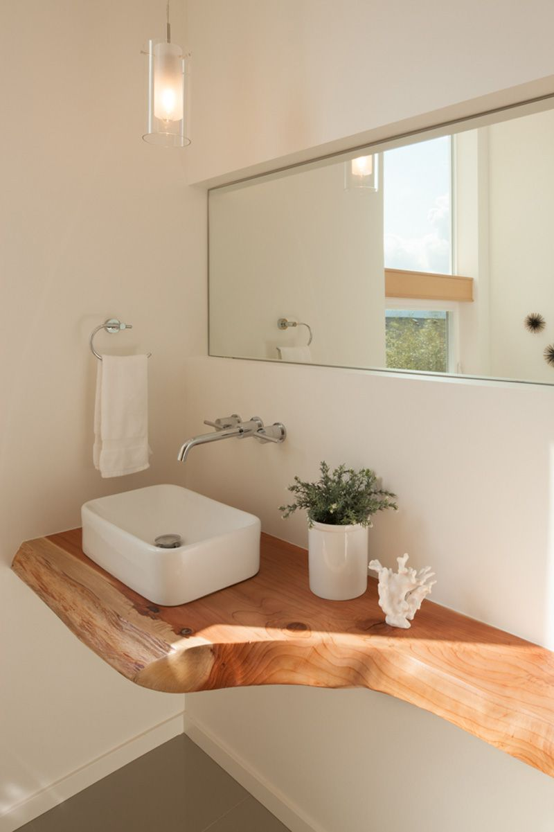 A Floating Natural Wood Countertop Features In This Bathroom