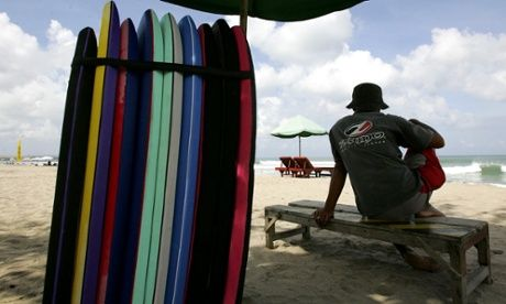 """A surf board lender waits for customers at Kuta beach. Photograph: Dimas Ardian/Getty Images. From the article """"Who invited you to Bali?"""" published by The Guardian online."""