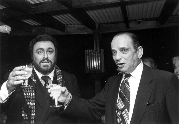 Luciano Pavarotti raising a glass for toasting with an unidentified man during a charity event. Fort Lauderdale, Florida. 1980s. Photographer: Roy Erickson. State Archives of Florida, Florida Memory