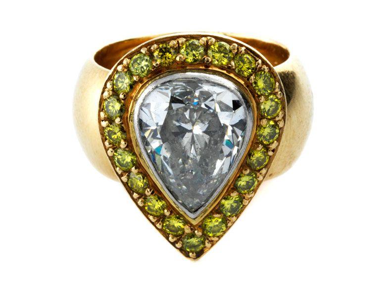 Ringweite: 52. Gewicht: ca. 12,4 g. GG 750. Außergewöhnlicher, aparter Ring mit hinterlegtem Diamantropfen, ca. 3 ct Cape/ P2, umrahmt von gelb-grünen...