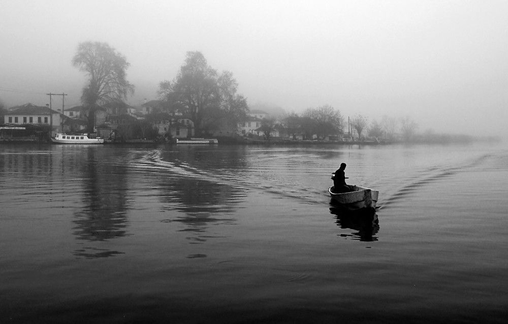 Crossing the misty lake by Hercules Milas | Redbubble #Greece #Greek #Ioannina #Giannena #lake #Pamvotis #Pamvotida #lakes #islet #islets #Nisaki #Epirus #Ipeiros #boat #boats #boatman #boatmen #fog #foggy #mist #misty #winter #wintry #mainland #inland #atmosphere #atmospheric #peaceful #nature #natural #landscape #landscapes #moody #black #and #white #monochrome #greyscale #retro #vintage #travel #destinations #sights #sightseeing #attractions #ioannina-grecce Crossing the misty lake by Hercu #ioannina-grecce