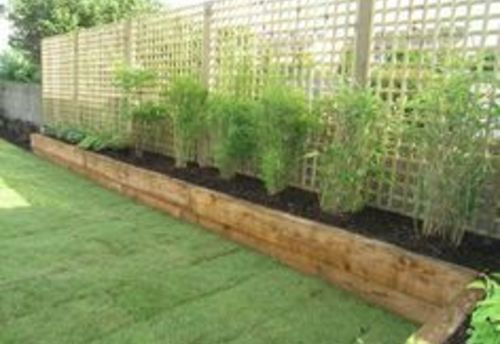 Raised flower bed along fence vegetable garden raised beds for Decking at end of garden