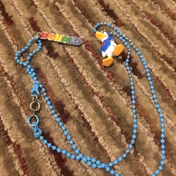 """Donald Duck Necklace Donald Duck necklace bought from Disneyland! Super cute for any Disney fan! There has been some wear to the beads, where the color faded slightly, showing the silver. It's not too noticeable. Has a small keychain thing that says """"DONALD."""" Disney Jewelry Necklaces"""