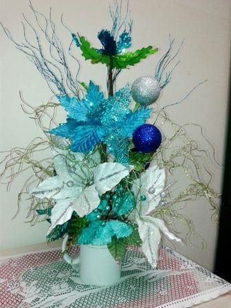 Centro de Mesa en colores azul, celeste, blanco y plateado, con unos toques de verde claro.