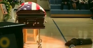 This picture breaks my heart. A dog mourns his fallen Hero.