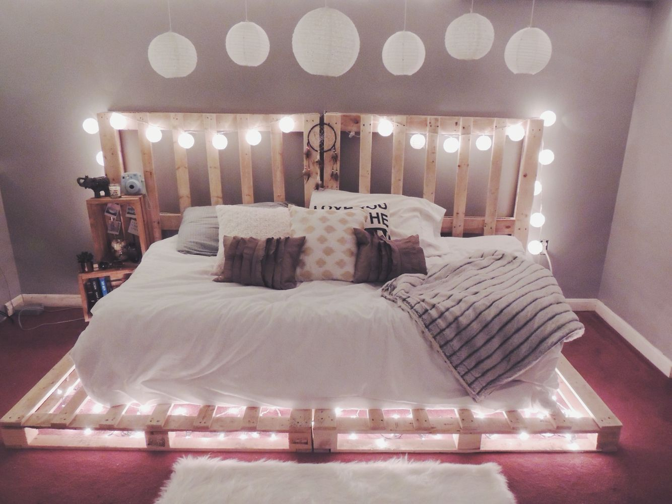 Use some old pallets and add christmas lights to make your for Pallet bed frame with side tables
