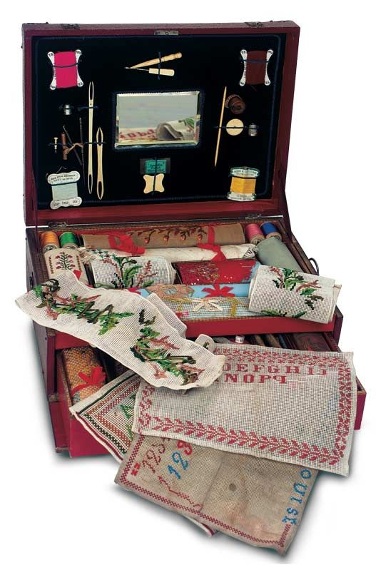 A wooden-framed box. Is covered with burgundy faux-leather and decorated with rich silver mounts and corners. It hinges open to reveal a two-layered interior containing a number of sewing and handwork tools and accessories along with various canvas and linen needlework and alphabet samplers in various stages of completion. Excellent condition. French,circa 1890.