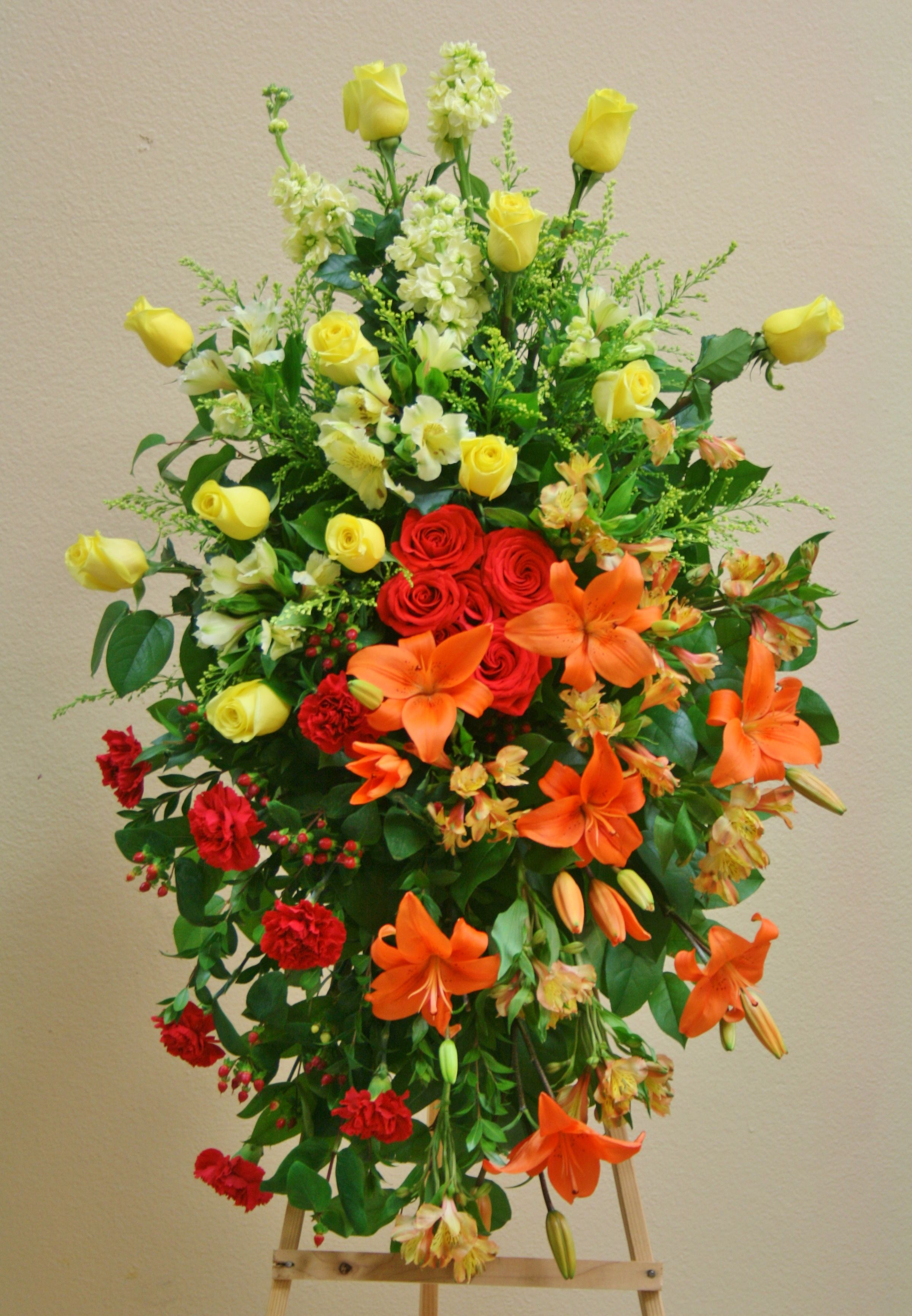 An Arrangement Of Flowers In Yellow, Orange And Red Includes