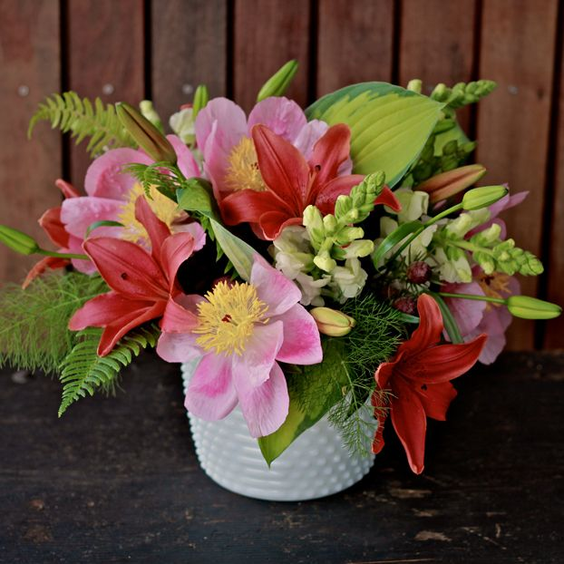 Red asiatic lilies, clematis, snap dragons & more in a beautiful Emerald Petals bouquet